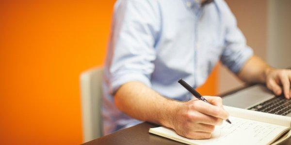 Businessman writing on paper pad