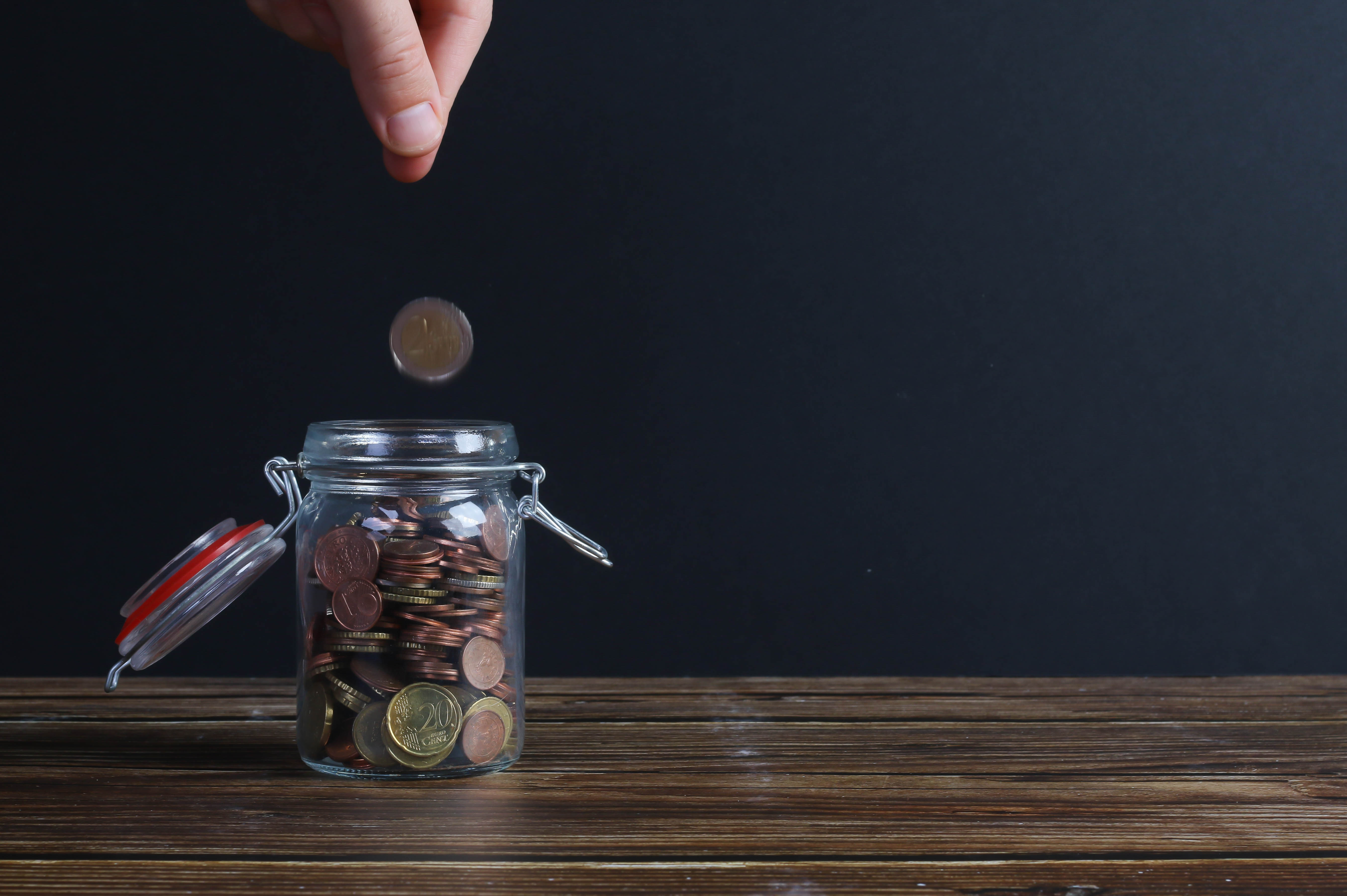 Coin being dropped in jar